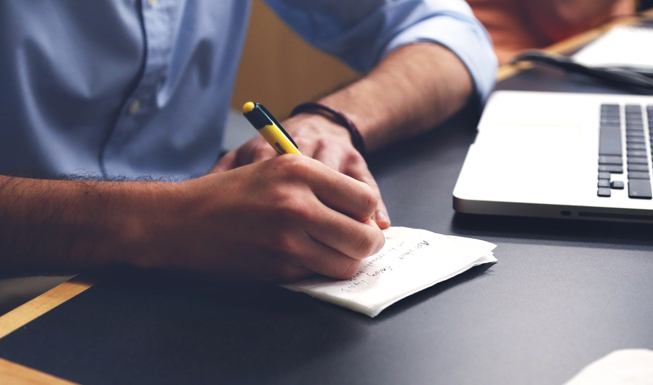 man writing notes about article outsourcing