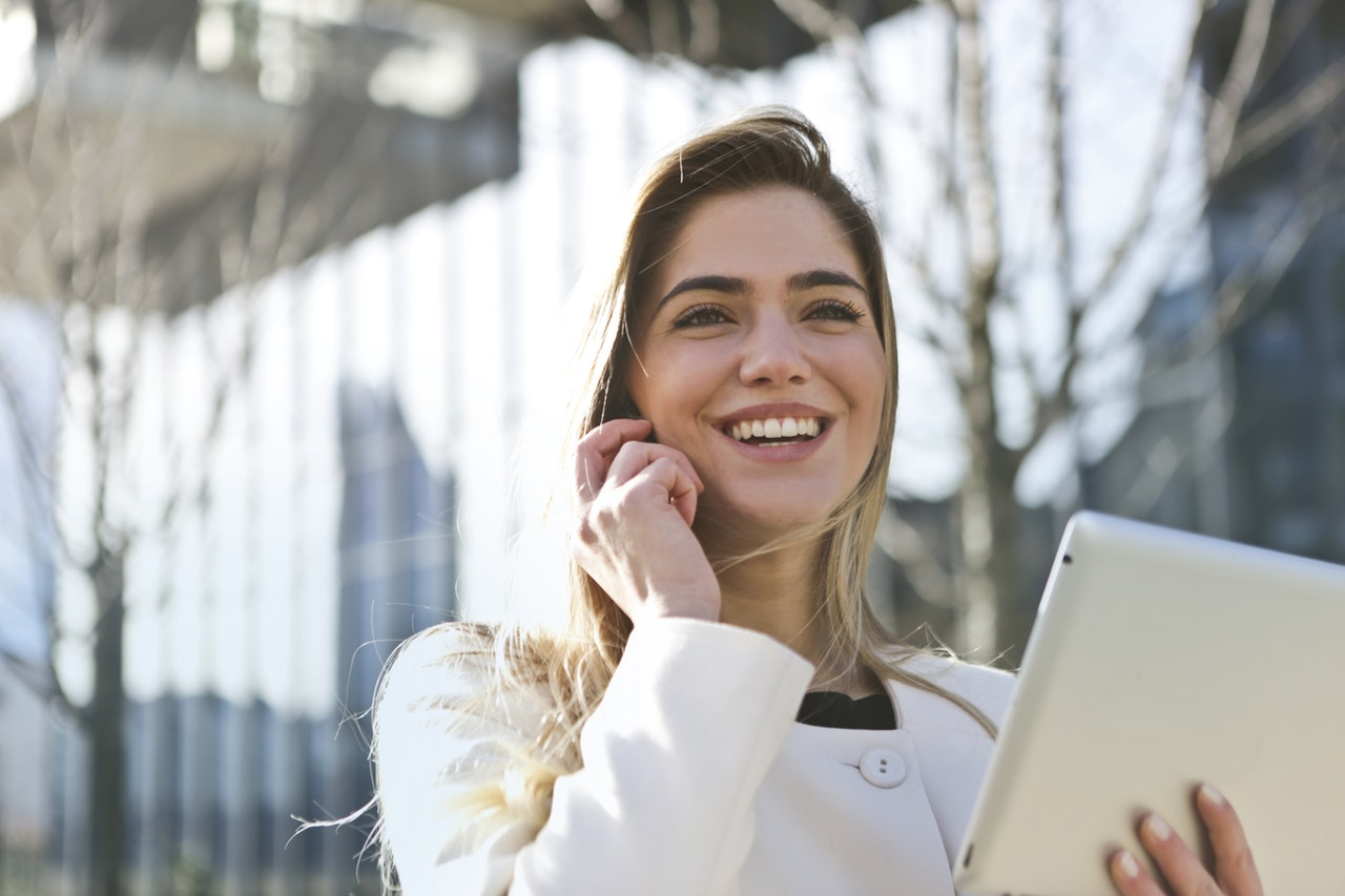 woman smiling while talking on the phone and holding a tablet equipped with the latest customer service trends