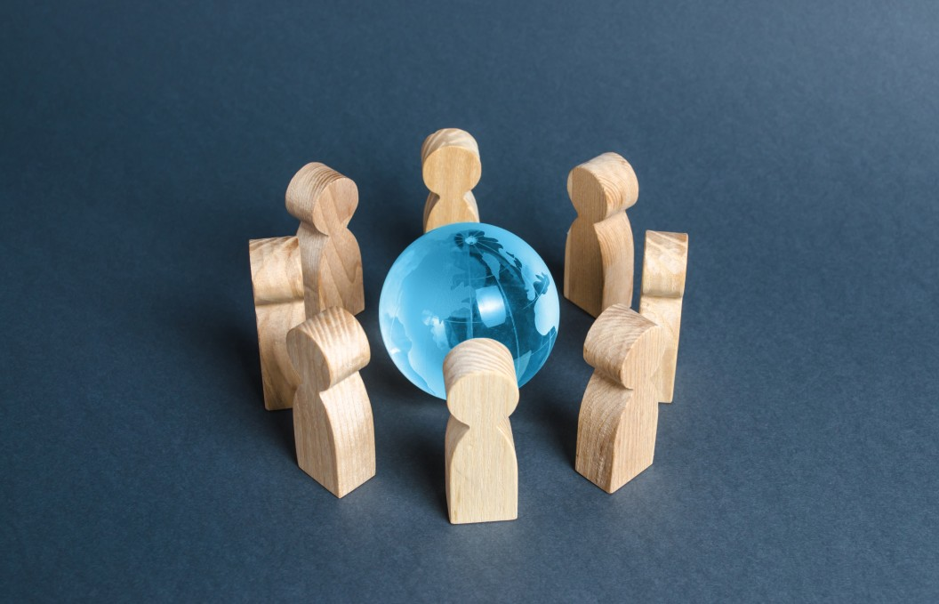 Wooden people surrounding blue globe showing what is bpo and its global effect