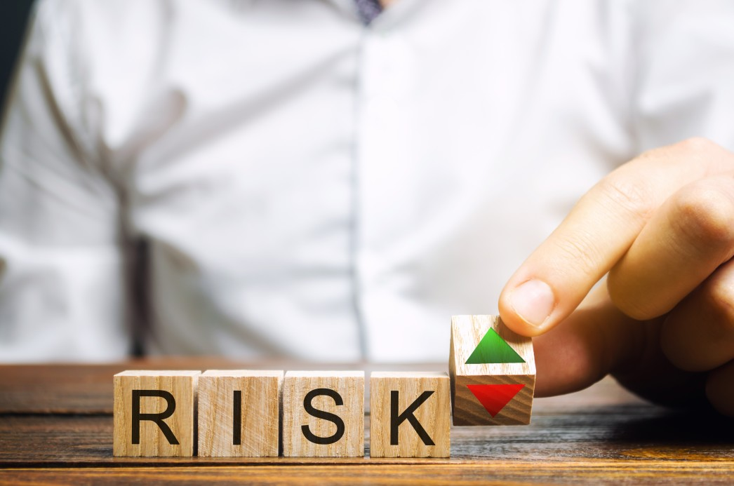 Risks written on wooden cubes for pros and cons of outsourcing