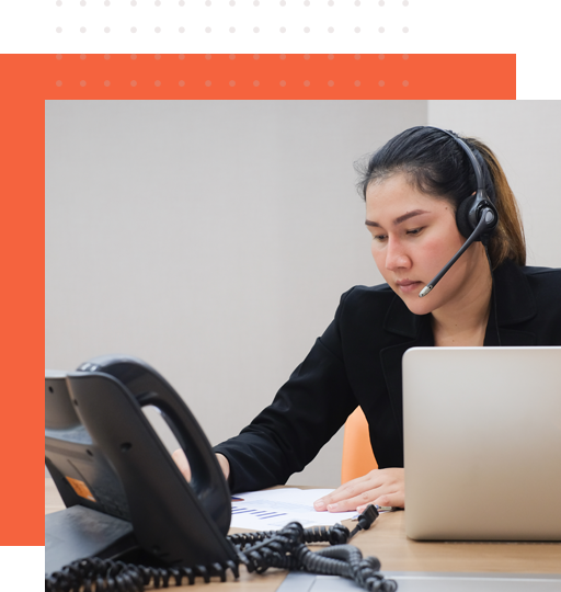 An asian female inbound sales representative in front of a desk phone
